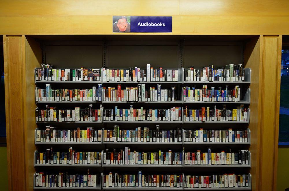 Na obrázku je audioknižnica - policky, kde sú namiesto klasických kníh audioknihy na CD