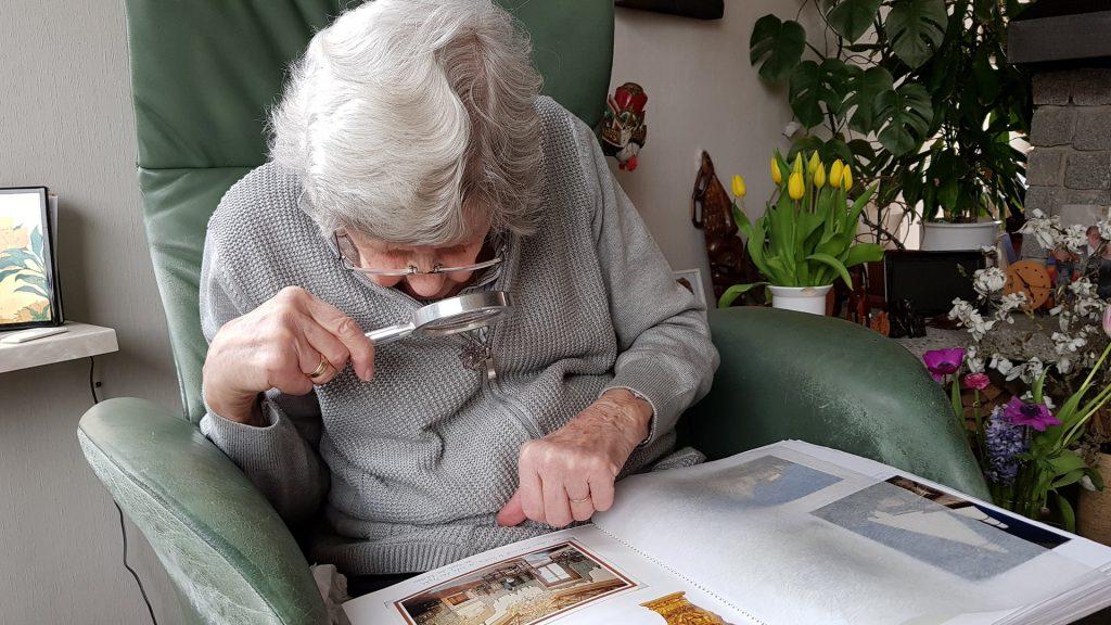 Staršia žena si pomocou lupy prezerá fotoalbum.