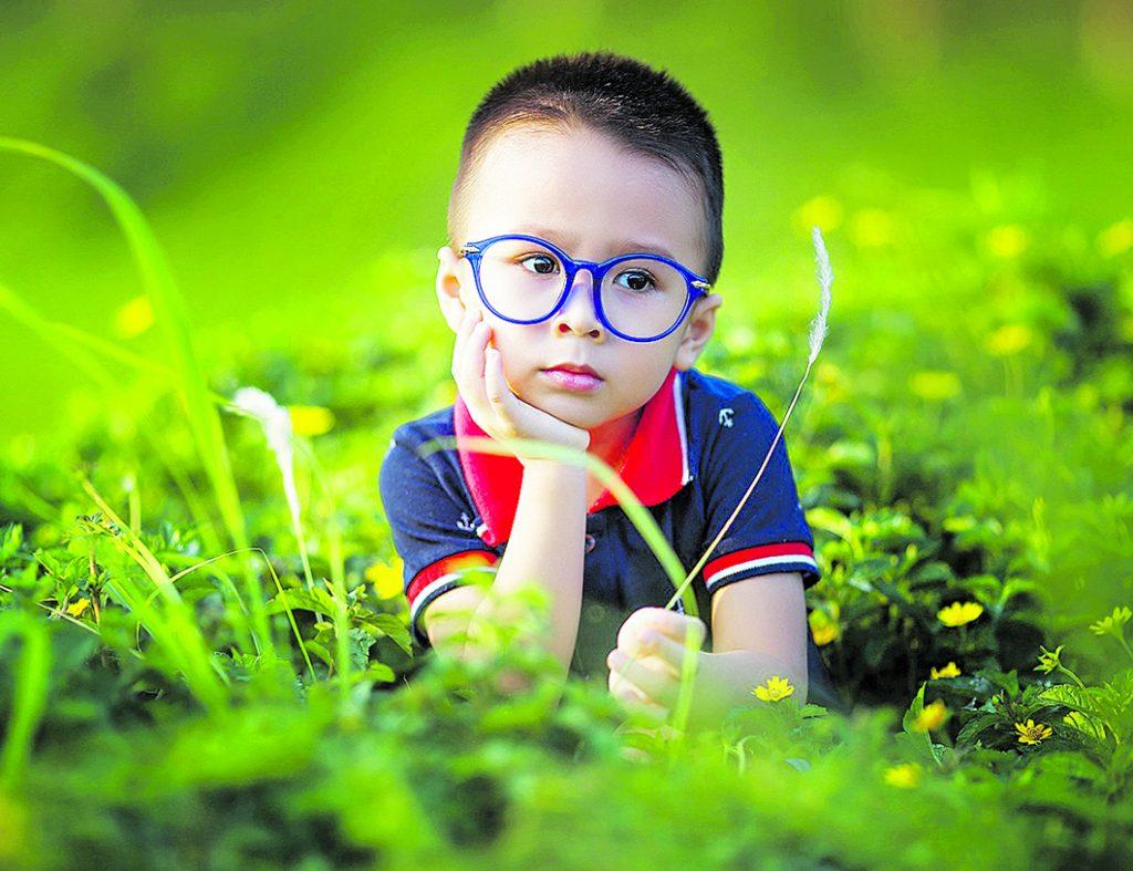 Dieťa ležiace v tráve má na tvári modré okuliare.