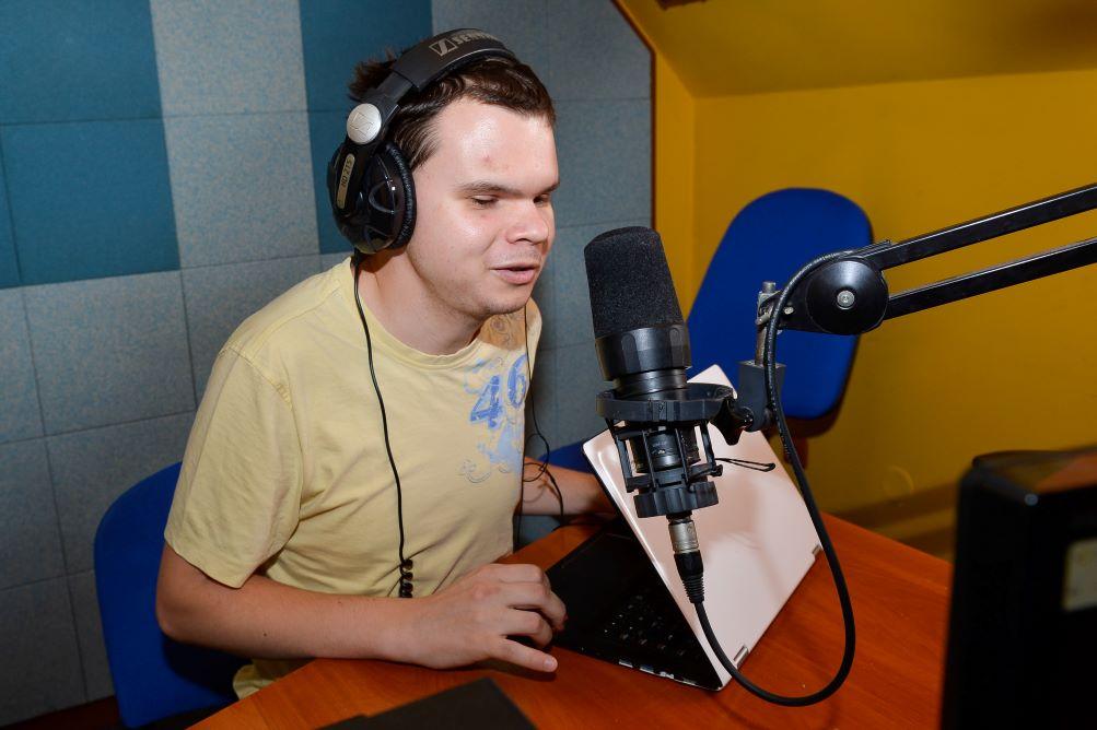 Ondrej sediaci za mikrofónom v rozhlasovom štúdiu.