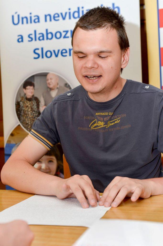 Ondrej číta text v Braillovom písme počas Braillovskej olympiády 2019.
