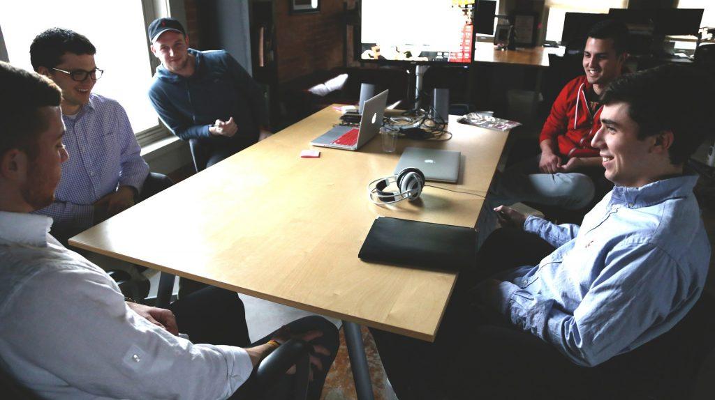 Na obr. je skupina mladých usmiatych mužov za jedným väčším stolom. Niektorí majú pred sebou notebooky.