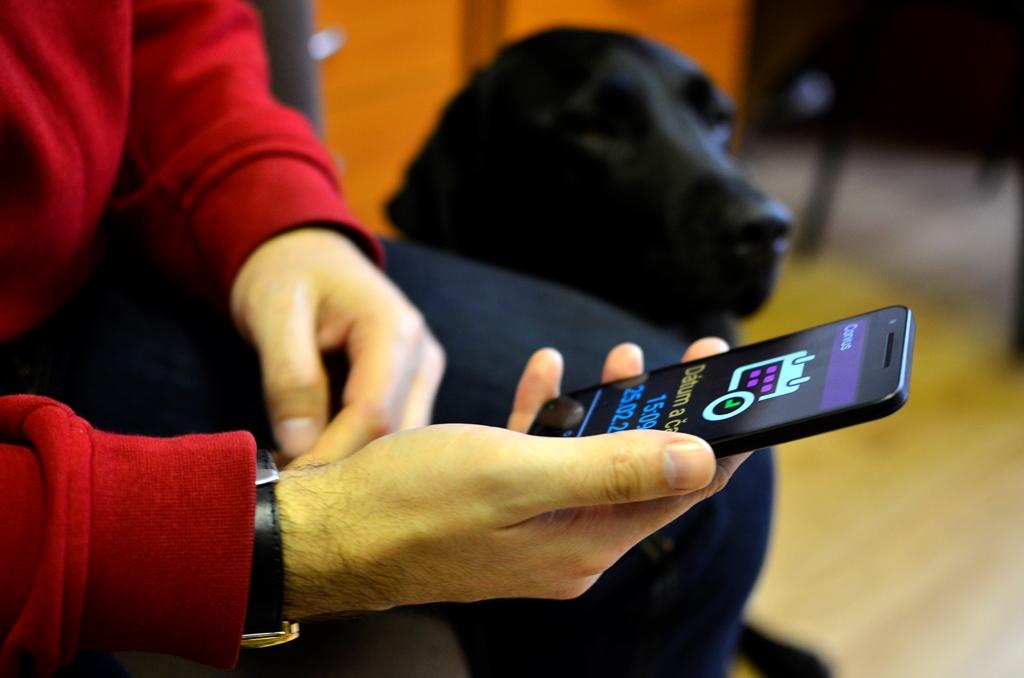 Na obrázku je detail rúk držiacich mobil so zapnutou aplikáciou. Vedľa človeka sedí vodiaci pes.
