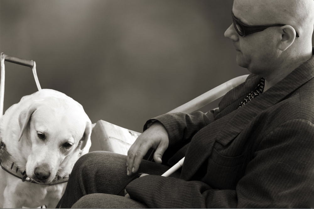 Na ČB zábere je sediaci muž a pri nohách mu sedí vodiaci pes.