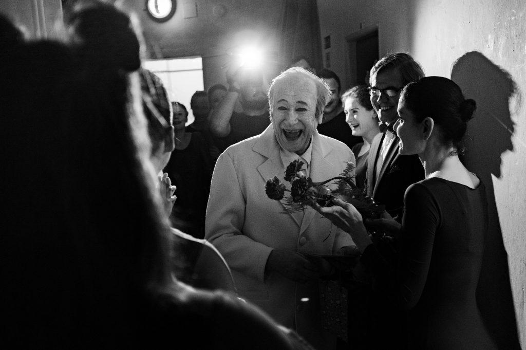 ČB záber, ústrednou postavou je mím Milan Sládek, ešte nalíčený, v zákulísí je v kruhu vysmiatych kolegov, vpredu mu žena podáva kvety.