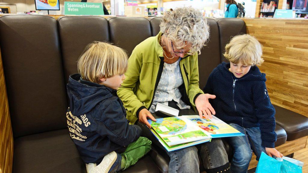 Na sedačke sedí stará mama a pri nej z každej strany chlapci (vnuci) a spoločne sa dívajú do atlasu.