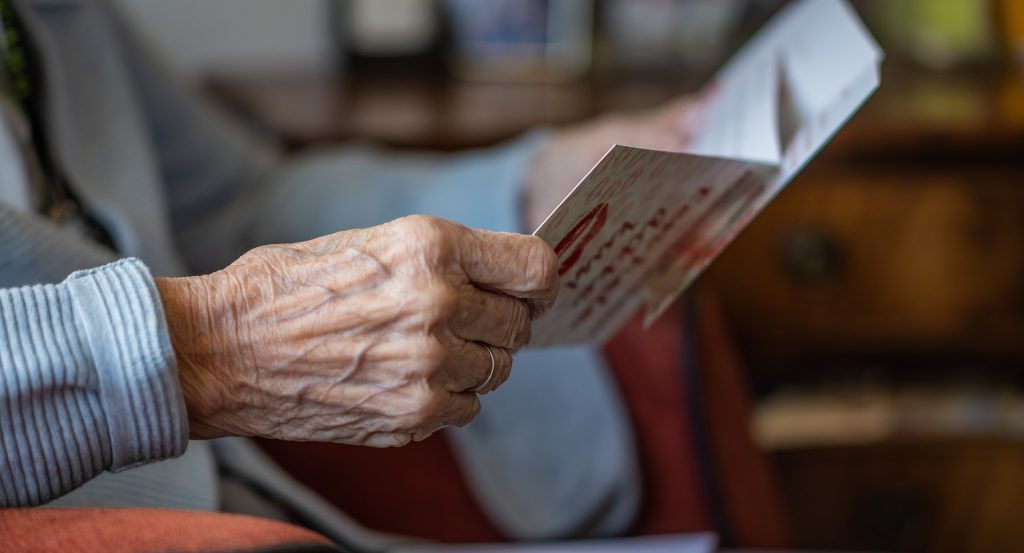 Detail na ruky seniorky, ktorá v nich má pozdrav.