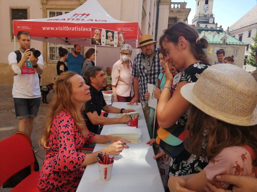 Na obrázku sú herci Diana Mórová a Peter Kočiš s návštevníkmi počas Bratislavských mestských dní. Nevidiacim podpisujú dotykové portréty.