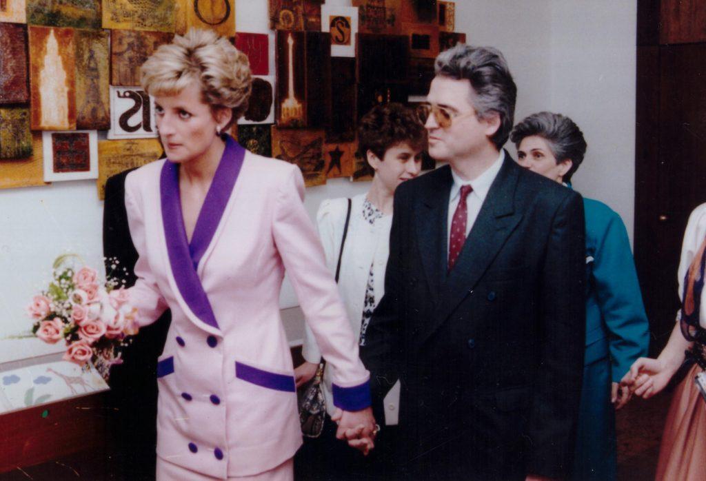Princezná Diana drží za ruku predsedu ÚNSS Branislava Mamojku a spoločne prechádzajú priestormi Mestskej knižnice.