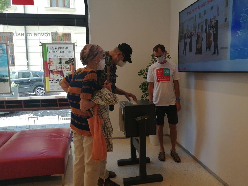V priestoroch TIC skúma hovoriacu kocku návštevník. Pri ňom stojí pracovník TIC a sprievod.