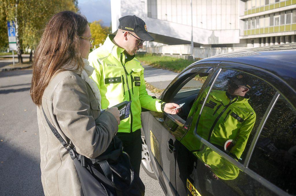 Dopravný policajt a informátorka stoja pri aute a komunikujú s vodičom